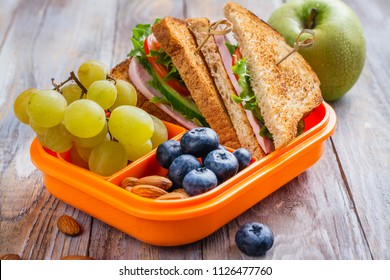 Healthy kids lunchbox with sandwich, fruits and orange juice