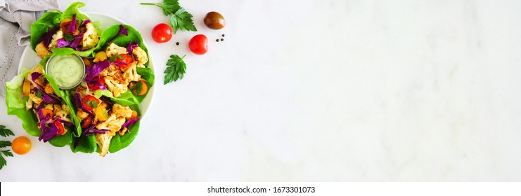 Healthy lettuce wraps with grilled cauliflower, cabbage and tomatoes. Top view corner border over a white marble banner background. Plant-based diet concept. Copy space.