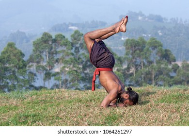 Healthy life exercise concept - athletic Indian man doing handstand outdoors in Kerala, South India