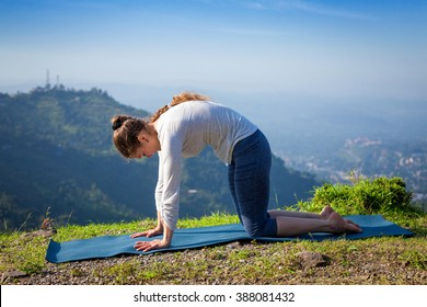 Healthy life exercise concept - Sporty fit woman practices yoga asana Marjariasana - cat pose outdoors in Himalayas