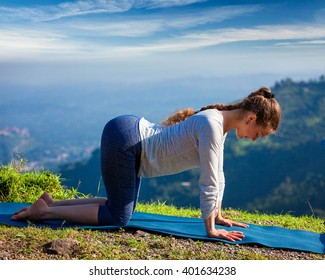 Healthy life exercise concept - Sporty fit woman practices yoga asana bitilasana - cow pose outdoors in mountains
