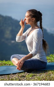 Healthy life exercise concept - Woman practices pranayama yoga breath control in lotus pose padmasana outdoors in Himalayas in the morning on sunrise. Himachal Pradesh, India