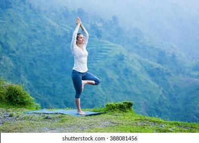 Healthy life exercise concept - Woman practices balance yoga asana Vrikshasana tree pose in Himalayas mountains outdoors. Himachal Pradesh, India. Panorama