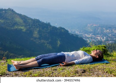 Healthy life exercise concept - Woman relaxes in yoga asana Savasana - corpse pose outdoors in Himalayas. Himachal Pradesh, India