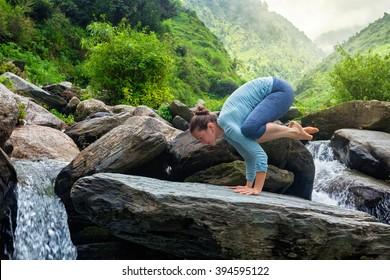 Healthy life exercise concept - Woman doing Bakasana asana crane pose arm balance outdoors at waterfall