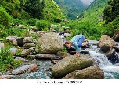 Healthy life exercise concept - Woman doing Kakasana asana - crow pose arm balance outdoors at tropical waterfall
