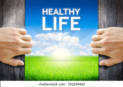 """Healthy Life. Hand opening an old wooden door and found wording """"Healthy Life."""" over green field and bright blue Sky Sunrise."""