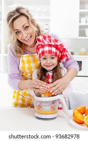 Healthy life - woman and little girl pressing fresh orange juice