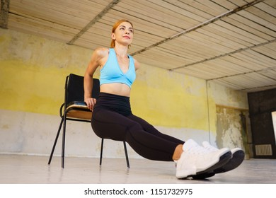 Healthy lifestyle, activity, fitness, sport. Woman doing reverse push ups using chair. Back and arms workout without equipment in gym