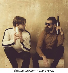 healthy lifestyle against the unhealthy. friendship of stylish friends talking and drinking on beige wall. Handsome model in sweater with milk or yogurt bottle and bearded man in sunglasses with