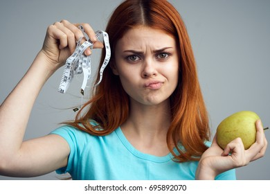 Healthy lifestyle, apple fruit, woman on a diet, measuring tape