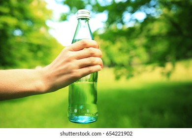 Healthy lifestyle background. Bottle of fitness water in hand close-up. Girl holding bottle of water on green nature background.