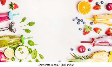 Healthy lifestyle background with various colorful smoothie drinks in bottles, blender and ingredients on white wooden. Detox and diet food concept.