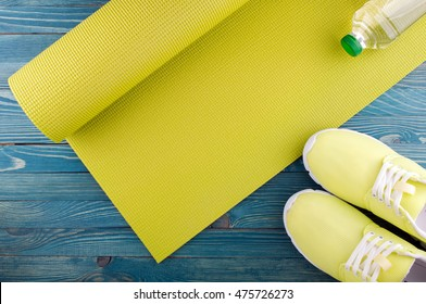 Healthy lifestyle background. Yoga mat, sport shoes, bottle of water on wooden background. Concept healthy and sport life. Top view