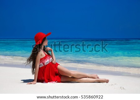 6ef430c5ea Beautiful carefree woman in hat enjoying exotic sea, brunette lying on  tropical beach at summer holiday. Attractive girl in red dress resting.