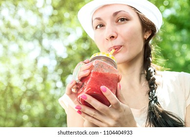 Healthy lifestyle. Beautiful smiling vegetarian woman drinking fresh raw detox vegetable or berry juice. refreshing with glass of red cranberry and strawberry smoothie on summer day, Diet Concept.