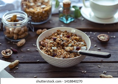 Healthy lifestyle breakfast bowl plate with granola and spoon on brown wooden table background, cereal granola food with nuts seed organic muesli morning diet oat meal for health care concept