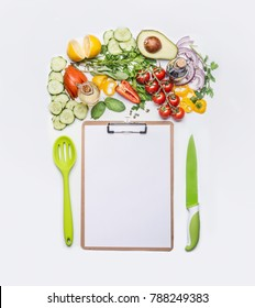 Healthy lifestyle and clean eating concept.  Various fresh salad vegetables with cooking spoon and knife around clipboard with blank paper . Copy space for shopping list, dieting plan or menu