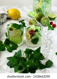 Healthy lifestyle. Cold and refreshing infused water with lime, mint, strawberry and cucumber in a glass. Bunch of fresh mint in the foreground