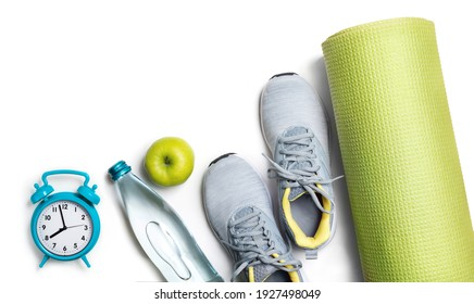 Healthy lifestyle concept, balance sport and health. Sport or athlete's equipment on white background. Sneakers, mat, alarm clock, bottle of water, apple Lay flat, top view