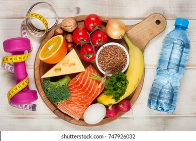 Healthy lifestyle concept. Dumbbell, bottle of water and healthy organic food on wooden table