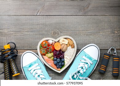 Healthy lifestyle concept with food in heart and sports fitness accessories