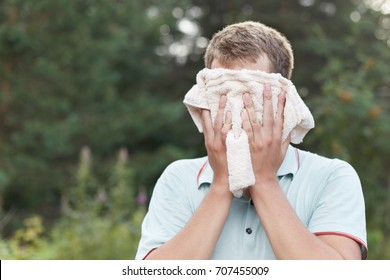 Healthy lifestyle concept. Headshot of young Caucasian sportsman wearing blue polo t-shirt with athletic body standing in forest morning sun is wet after training activity, covering  face with towel.