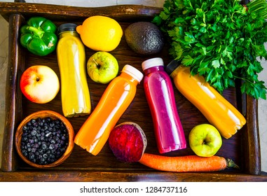 Healthy lifestyle concept with juice bottles, vegetables and fruits on wooden tray, top view, healthy living fitness concept