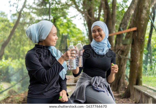Healthy Lifestyle Concept, Malay Muslim lady wearing hijab outdoor resting and drink water