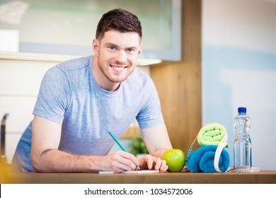 healthy lifestyle concept - man at home writing down training and sports nutrition plans