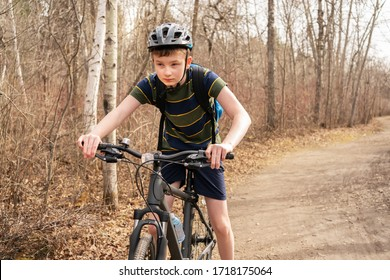 Healthy lifestyle concept. Teen boy wearing helmet rides his bike on the path in forest during spring time. Boy wearing striped t shirt and dark blue shorts riding sport bike in city park in Canada.