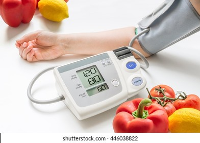 Healthy lifestyle concept. Woman is measuring blood pressure with monitor. Vegetables in background.