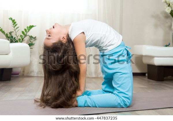 Healthy lifestyle concept. Yoga and Fitness. Joyful happy yoga little girl working out in living room. Beautiful funny kid girl with long hair laughing while exercising at home. Side view portrait