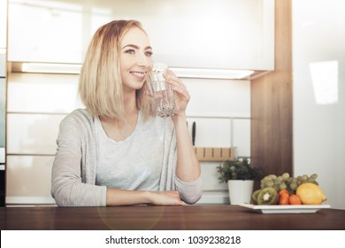 healthy lifestyle concept - young woman drinking water from glass in the kitchen