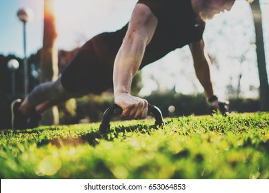 Healthy lifestyle concept.Functional training outdoors.Handsome sport athlete man doing pushups in the park on the sunny morning. Blurred background.Horizontal.Flares,sunlight effect