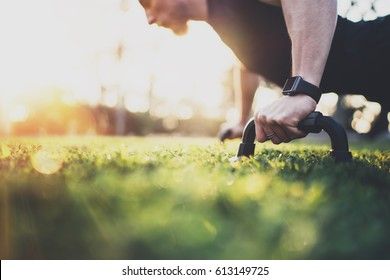Healthy lifestyle concept.Muscular athlete exercising push up outside in sunny park. Fit shirtless male fitness model in   exercise outdoors.Sport fitness man doing push-ups.Blurred background