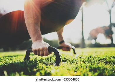 Healthy lifestyle concept.Training outdoors.Handsome sport man doing pushups in the park on the sunny morning. Blurred background. Horizontal closeup.Flares,sunlight effect