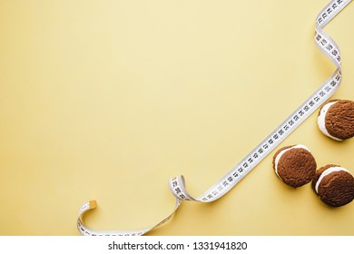 healthy lifestyle decision, diet restrict, carbs reduce, sugar, sweets. chocolate cookie background with measure tape, copy space. fitness, nutritionist, dietitian blog design concept