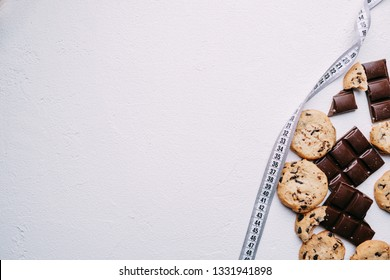 healthy lifestyle decision, diet restrict, carbs reduce, sugar, sweets. chocolate and cookie background and measure tape with copy space. fitness, nutritionist, dietitian blog design concept