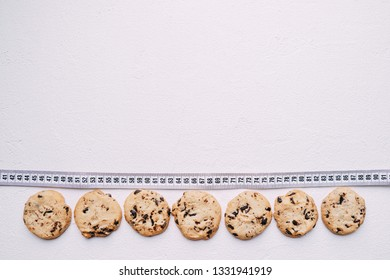 healthy lifestyle decision, diet restrict, carbs reduce, sugar, sweets. chocolate cookie background and measure tape with copy space. fitness, nutritionist, dietitian blog design concept