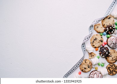 healthy lifestyle decision, diet restrict, carbs reduce, sugar, sweets. candy and cookie background with measure tape, copy space. fitness, nutritionist, dietitian blog design concept