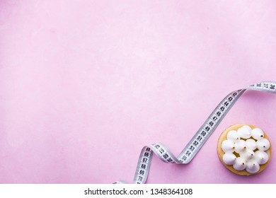 healthy lifestyle decision, diet restrict, carbs reduce, sugar, sweets. delicious cake on pink background and measure tape with copy space. fitness, nutritionist, dietitian blog design concept