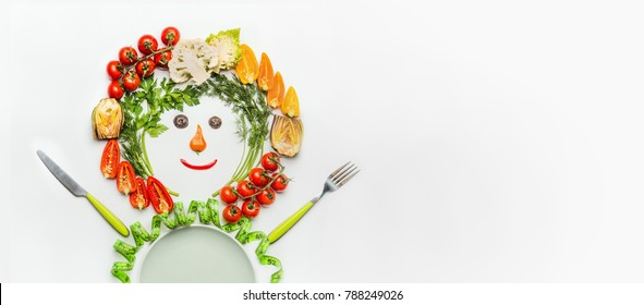 Healthy lifestyle and dieting concept. Friendly Man made of salad vegetables , plate, cutlery and measuring tape on white desk background, top view, place for text. Clean food and vegetarian eating