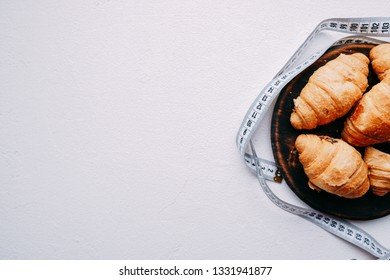 healthy lifestyle, dieting, weight loss, balanced food. sweet croissants and measure tape. diet and fitness blog design concept