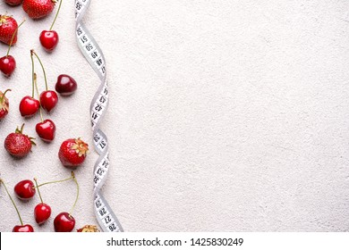 healthy lifestyle, dieting, weight loss, balanced food. Cherries and fresh juicy strawberries and measure tape. diet and fitness blog design concept