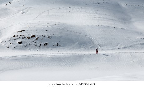 Healthy lifestyle, distant hiker walking forward on snowy mountain