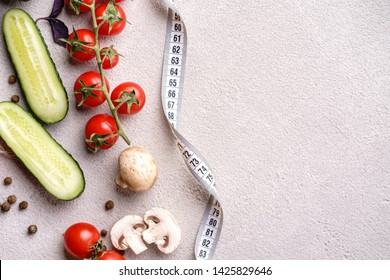 Healthy lifestyle and eating decision, motivation, vegetarian menu, diet. Vegetables and herbs background and measure tape with copy space. fitness, nutritionist, dietitian blog design concept