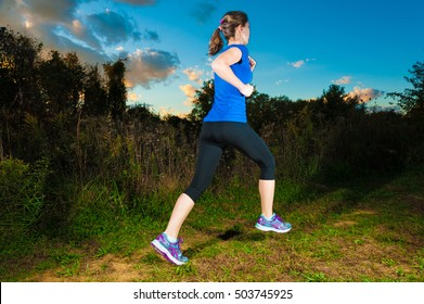 healthy lifestyle fitness sporty woman runner running outdoors with evening sky.