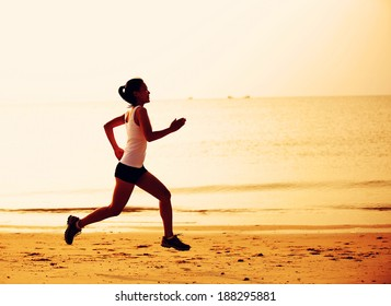 healthy lifestyle fitness woman jogging at sunrise/sunset beach