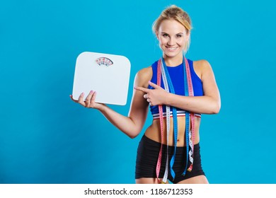 Healthy lifestyle. Fitness woman with many measure tapes holding weight scale studio shot blue background